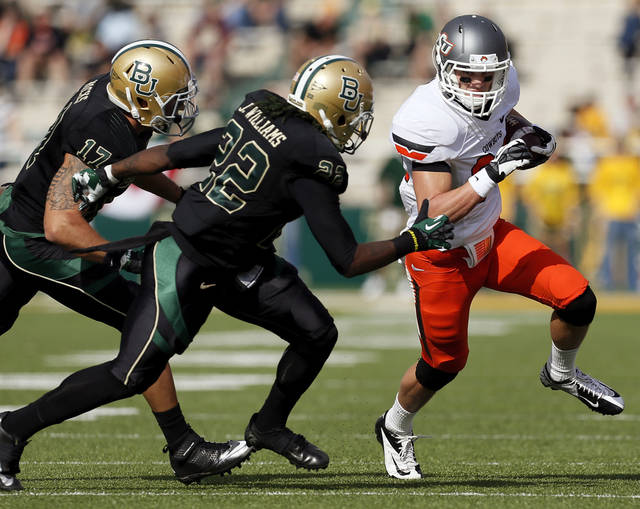 Oklahoma State's Austin Hays (84) tries to get past Baylor's Joe Williams (22) and Mike Hicks (17) in the first quarter during a college football game between the Oklahoma State University Cowboys (OSU) and the Baylor University Bears at Floyd Casey Stadium in Waco, Texas, Saturday, Dec. 1, 2012. Photo by Nate Billings, The Oklahoman