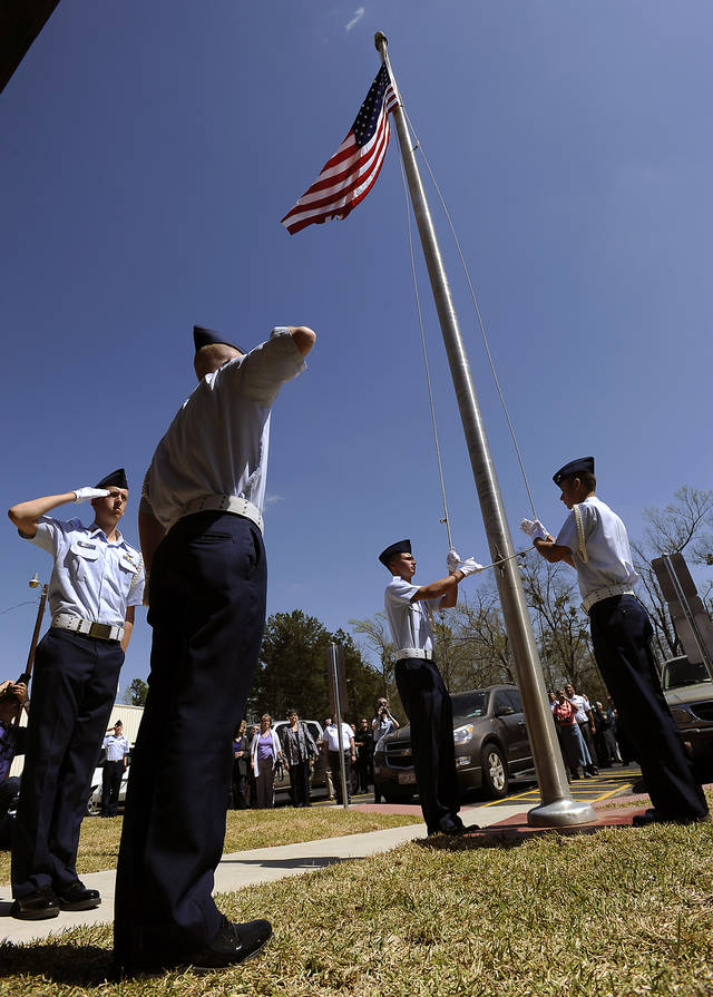 Civil Air Patrol cadet color guard members Master Sgt. Alessandro Liona, left, and Senior Master Sgt. Joe Korona salute as Staff Sgt. Dave Printz and Staff Sgt. Damon Printa raise the flag for the first time Saturday, March 16, 2013, during dedication ceremonies for the Gen. D.H. Byrd Training Center in the former Army National Guard Armory at A.L. Mangham Regional Airport in Nacogdoches, Texas. The facility will serve as a regional and state training center for C.A.P. emergency response teams and for cadet aerospace educational programs. (AP Photo/The Daily Sentinel, Andrew D. Brosig)MANDATORY CREDIT ORG XMIT: TXNAC101