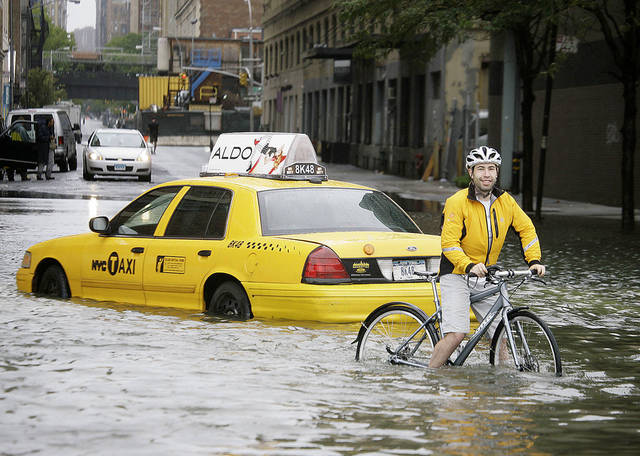 A bicyclist makes his way past a stranded taxi last August on a flooded New York City street as Tropical Storm Irene passes through the city. As sea levels rise on the East Coast, storms and related flooding will be even more damaging, scientists say. AP File Photo
