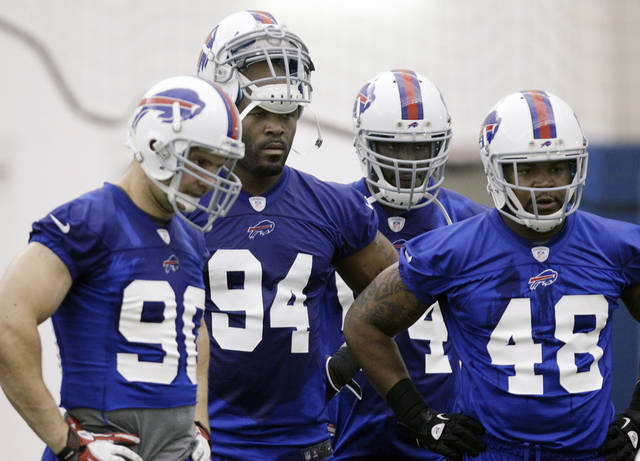 Buffalo Bills' Mario Williams (94) listens to a coach with teammates Chris Kelsay (90), Kyle Moore (54) and Robert Eddins (48) during NFL football practice in Orchard Park, N.Y., Tuesday, May 29, 2012. (AP Photo/David Duprey)