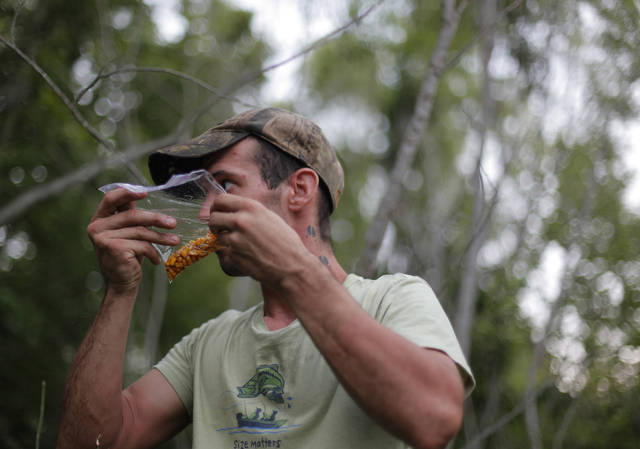 Johnny Heskett smells hog bait during a hunting trip near Indianola, Okla., Friday, July 6, 2012.  The bait was a mixture of corn, maple syrup, and diesel fuel.  Photo by Garett Fisbeck, The Oklahoman