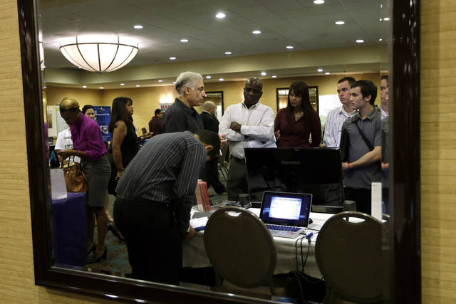 Robert Orkin of the company TxT-Alert, third from left, talks with job seekers Sept. 17 during a job fair held by National Career Fairs in Fort Lauderdale, Fla. AP Photo