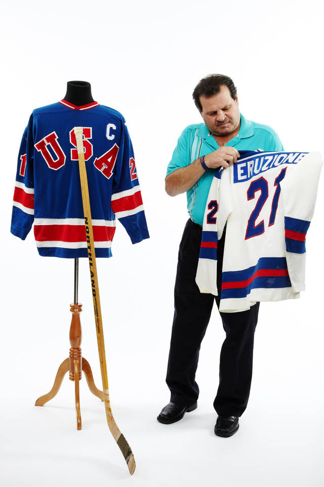 In this photo taken Dec. 12, 2012 and provided by Heritage Auctions in Dallas, former United States Olympic hockey player Michael Eruzione poses in Dallas, with with jerseys and the hockey stick from his sensational winning goal against the Soviet Union hockey team at the 1980 Winter Olympics. Chris Ivy of Heritage Auctions said the No. 21 jersey went for $657,250 on Saturday. The stick Eruzione used to score the winning goal sold for $262,900, more than five times its pre-sale estimate. The buyers' names were not immediately available. (AP Photo/Courtesy of Heritage Auctions)