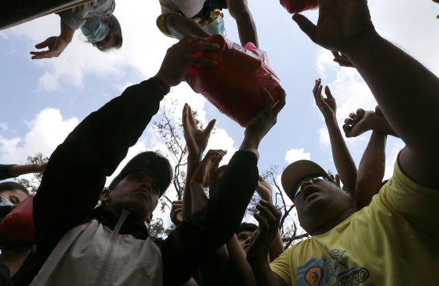Residents affected by typhoon Bopha crowd as relief goods are distributed at New Bataan township, Compostela Valley in southern Philippines Sunday Dec. 9, 2012. The number of missing in the wake of the typhoon that devastated parts of the southern Philippines has jumped to nearly 900 after families and fishing companies reported losing contact with more than 300 fishermen in the South China Sea and Pacific Ocean, officials said Sunday. (AP Photo/Bullit Marquez)