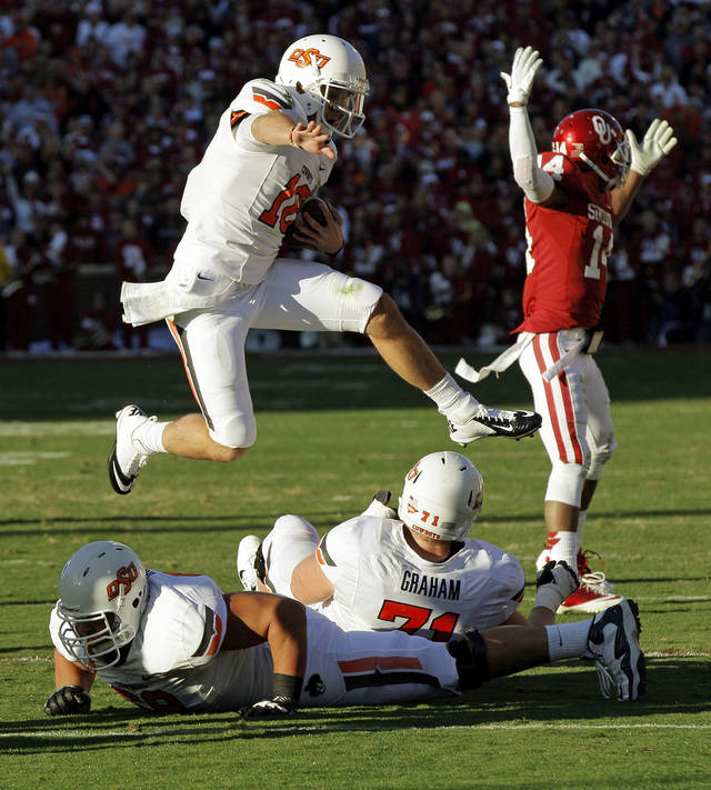 Oklahoma State's Clint Chelf (10) leaps over teammates Lane Taylor (68) and Parker Graham (71) after catching a pass as Oklahoma's Aaron Colvin (14) reacts in the second quarter during the Bedlam college football game between the University of Oklahoma Sooners (OU) and the Oklahoma State University Cowboys (OSU) at Gaylord Family-Oklahoma Memorial Stadium in Norman, Okla., Saturday, Nov. 24, 2012. Photo by Nate Billings , The Oklahoman