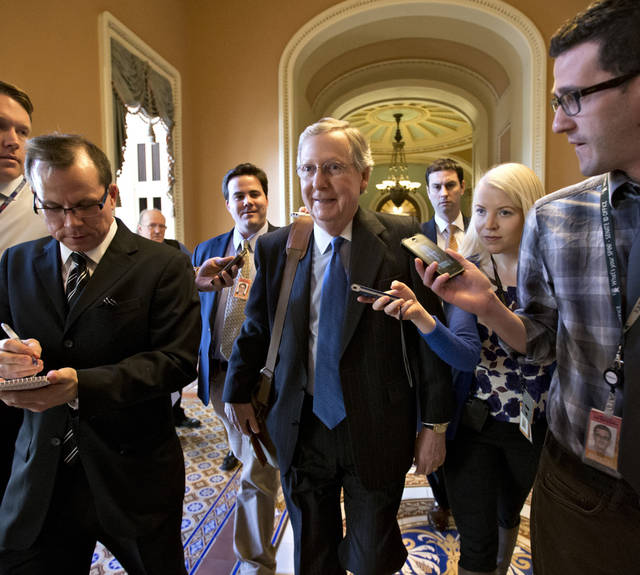 "Senate Minority Leader Mitch McConnell of Kentucky, center, arrives at his office in the Capitol as he and Senate Majority Leader Harry Reid of Neveda, try to negotiate a legislative solution to avoid the so-called ""fiscal cliff"" in Washington, Sunday, Dec. 30, 2012.   (AP Photo/J. Scott Applewhite)"