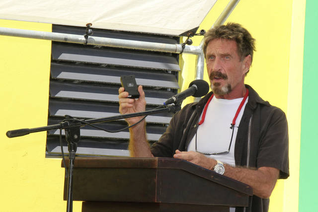 "FILE - In this Nov. 8, 2012 file photo, John McAfee speaks at a ceremony for the official presentation of equipment at the San Pedro Police Station in Ambergris Caye, Belize.  McAfee, 67, has been identified as a ""person of interest"" in the killing of his neighbor, 52-year-old Gregory Faull. Police are urging McAffe to come in for questioning. The anti-virus company founder  said on Monday, Dec. 3, 2012, he has left Belize and is still on the run, hiding from police out of fear they want to kill him.  (AP Photo/Ambergris Today Online-Sofia Munoz, File)"
