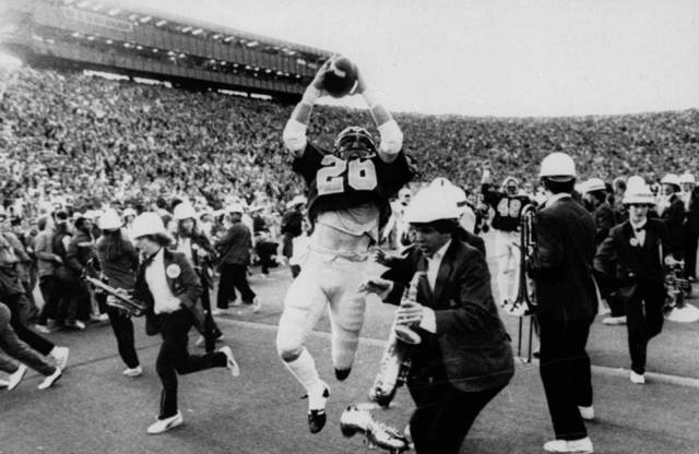 FILE - In this Nov. 20, 1982, file photo, California's Kevin Moen (26) leaps with the ball in the air after scoring their winning touchdown while the Stanford band runs to get out of his way during an NCAA college football game in Berkeley, Calif. Thirty years since those laterals lifted the long running rivalry into national stardom, the 115th Big Game at remodeled Memorial Stadium on Saturday, Oct. 20, 2012, will be a chance for the next generation of players to make their own memories. (AP Photo/The Tribune, Robert Stinnett, File) MANDATORY CREDIT