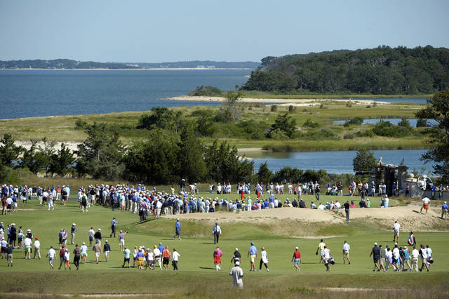 Fans gather around the 17th green during the Walker Cup Match golf tournament held at the National Golf Links of America on Saturday, Sept. 7, 2013 in Southampton, N.Y.(AP Photo/Kathy Kmonicek)