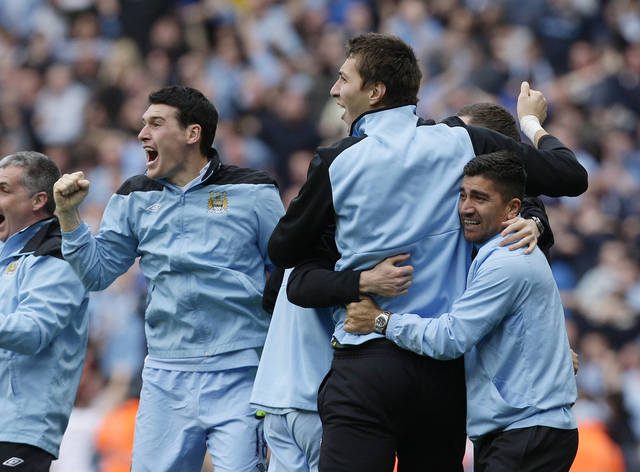 Manchester City's Gareth Barry, left, celebrates with team members after winning the English Premier League title after their soccer match against Queens Park Rangers at the Etihad Stadium, Manchester, England, Sunday May 13, 2012. (AP Photo/Jon Super)