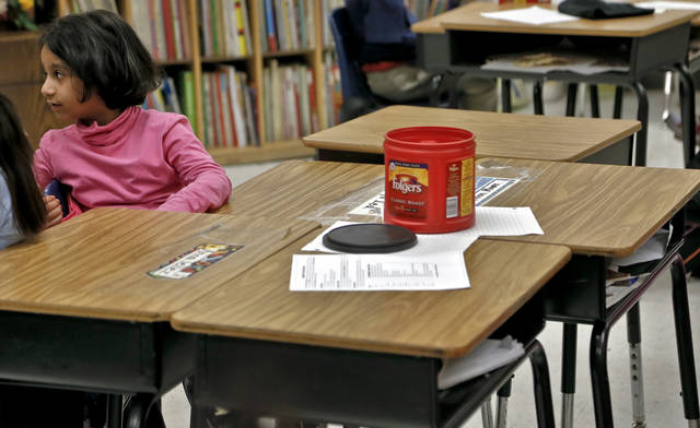 Desks sit empty around first grader Safiya Led as she listens to a story read by her teacher Michelle Kenery at North Highland Elementary on Tuesday, Jan. 15, 2013, in Oklahoma City, Okla. The school has been one of the most effected in the metro by the arrival of flu season. Photo by Chris Landsberger, The Oklahoman.