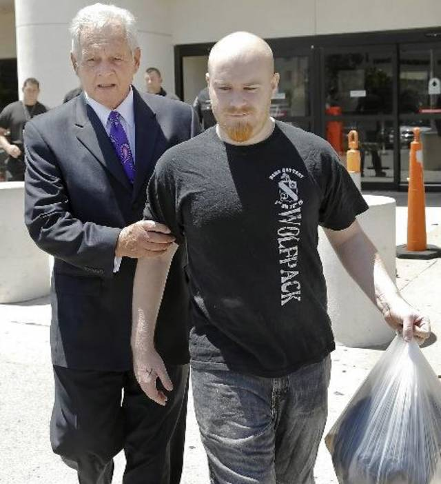 Attorney Irven Box, left, walks with Justin Adams after Adams was released July 25 on $100,000 bond from the Oklahoma County jail in Oklahoma City. Photo by Chris Landsberger, The Oklahoman Archvies