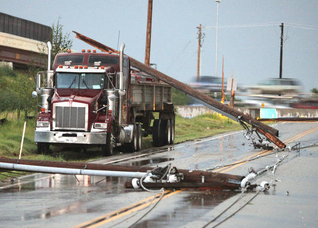 Power poles and lines that fell at Rock Creek Road and I-35 lean against a truck on Tuesday, June 14, 2011, in Norman, Okla.  Photo by Steve Sisney, The Oklahoman