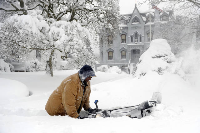 George Ransom pushes his snowthrower on the sidewalk along Broadway in front of St. Patrick's School, Saturday, Feb. 9, 2013, after a snow storm in Norwich, Conn. (AP Photo/The Day, Sean D. Elliot)  MANDATORY CREDIT ORG XMIT: CTNLD201