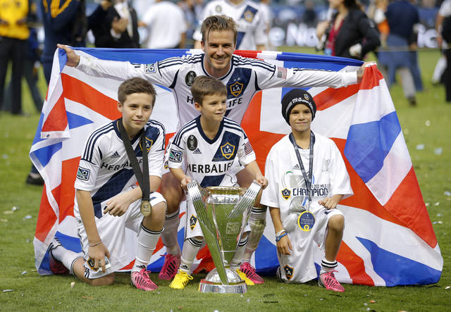 FILE - In this  Saturday, Dec. 1, 2012 file photo Los Angeles Galaxy's David Beckham, top center, of England, poses with his sons, from left, Brooklyn, Romeo and Cruz after the Galaxy's 3-1 win in the MLS Cup championship soccer match against the Houston Dynamo in Carson, Calif. David Beckham's eldest son just might be the next person in his family to play in the Premier League. Brooklyn Beckham, the oldest of Beckham's four children at 13, is having a trial with London club Chelsea and played in an under-14 game on Tuesday at the team's training base, people familiar with the situation told The Associated Press.  (AP Photo/Jae C. Hong)