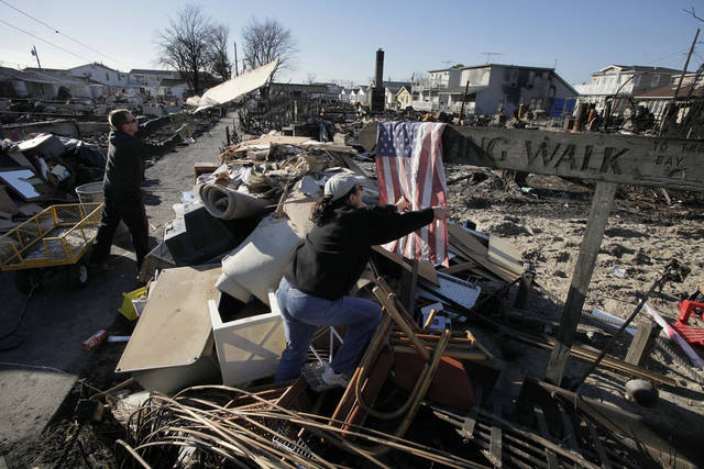 <p>Louise McCarthy drapes an American flag that she found on a charred street sign in the Breezy Point section of the Queens borough of New York as another resident throws away wood from a damaged home, Wednesday, Nov. 14, 2012. A fire destroyed more than 50 homes in the oceanfront community during Superstorm Sandy. (AP Photo/Mark Lennihan)</p>