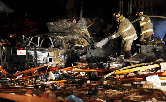 Firefighters spray water on a car Thursday in the garage of a house destroyed by a natural gas explosion.