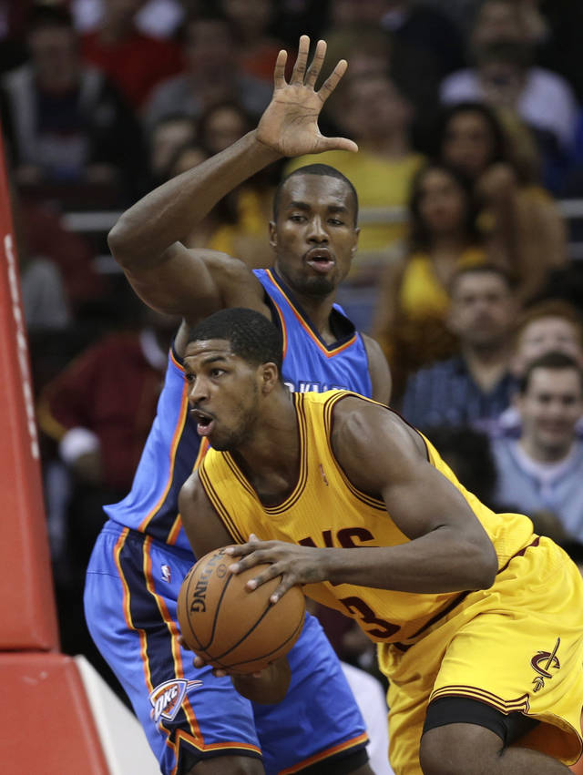 Cleveland Cavaliers' Tristan Thompson, front, drives past Oklahoma City Thunder's Serge Ibaka, from the Republic of Congo, during the first quarter of an NBA basketball game on Saturday, Feb. 2, 2013, in Cleveland. (AP Photo/Tony Dejak) ORG XMIT: OHTD104