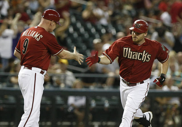 Arizona Diamondbacks' Jason Kubel, right, celebrates with third base coach Matt Williams in the first inning after hitting a solo home run against the Colorado Rockies during a baseball game on Wednesday, July 25, 2012, in Phoenix. (AP Photo/Rick Scuteri)