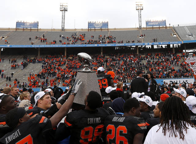 Oklahoma State holds the Heart of Dallas trophy following the Heart of Dallas Bowl football game between the Oklahoma State University (OSU) and Purdue University at the Cotton Bowl in Dallas,  Tuesday,Jan. 1, 2013. Photo by Sarah Phipps, The Oklahoman