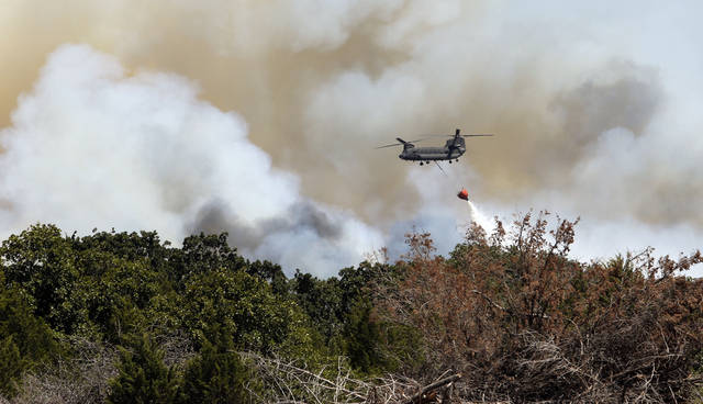 WILDFIRE: A helicopter drops water on a large grass fire east of 120th near Cemetery Road on Friday, Aug. 3, 2012, east of Norman, Okla.  Photo by Steve Sisney, The Oklahoman
