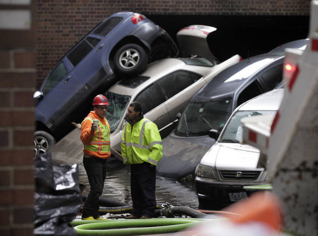 Cars that were uprighted and submerged by Superstorm Sandy remain at the entrance of a subterranean parking garage in New York's Financial District, as the water is pumped out, Friday, Nov. 2, 2012. . The cost of the storm could exceed $18 billion in New York alone.  (AP Photo/Richard Drew) ORG XMIT: NYRD124