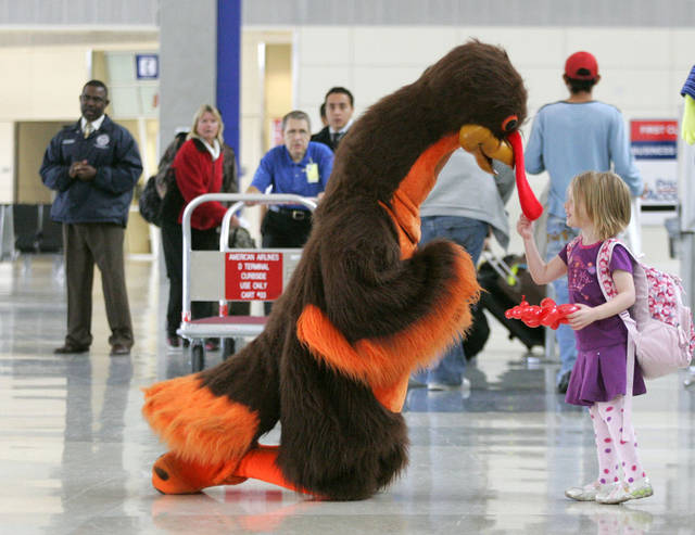 FILE -In this Wednesday, Nov. 26, 2008, file photo, Abby Harris, 4, checks the wattle on a turkey greeting passengers at Dallas-Fort Worth International Airport in Grapevine, Texas. Americans can expect airports to be busier and planes to be fuller than ever, according to a forecast by the main trade association for U.S. airlines on Wednesday, Nov. 7, 2012, two weeks ahead of the holiday. And fares are already more expensive than a year ago. (AP Photo/Donna McWilliam, File)