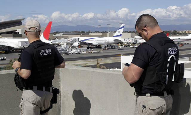 Departement of Homeland Security police officers keep an eye on planes at the Los Angeles International Airport Wednesday, Oct. 10, 2012. In an age when travelers have to toss bottled water at airport security checkpoints, what may be most striking about the arrest of a passenger from Japan wearing a bulletproof vest and flying with checked luggage loaded with a cache of weapons, shackles and body bags is that most of it wasn't illegal on the flight to the U.S. (AP Photo/Damian Dovarganes)