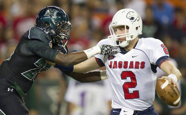Hawaii defensive back Marrell Jackson (25) gets a hold of Southern Alabama quarterback Ross Metheny (2) in the first quarter of an NCAA college football game Saturday, Dec. 1, 2012, in Honolulu.  (AP Photo/Eugene Tanner)