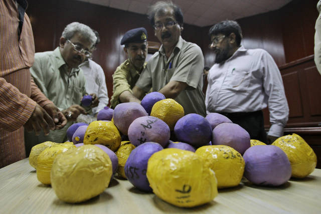 In this Friday, May 11, 2012 photo, customs officials looks at confiscated heroin wrapped in packages, following a news conference in Karachi, Pakistan. Iran, Pakistan and other countries in South Asia are fast becoming key players in the global methamphetamine market, with drug cartels taking advantage of the weak governance and law enforcement that have long fueled the region's heroin trade. (AP Photo/Shakil Adil)