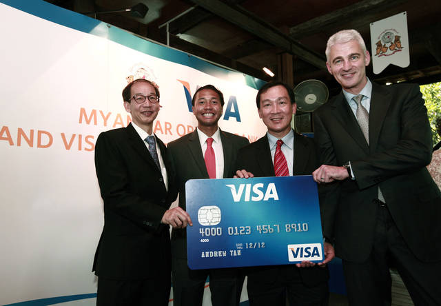 FILE - In this Thursday, Jan. 31, 2013 file photo, Paul Cook, right, head of Acceptance for Visa in Asia Pacific, central Europe, Middle East and Africa; Somboon Krobteeranon, second from right, country manager of Myanmar and Thailand; and two unidentified officials pose for photo with an oversized Visa card during a launching ceremony of the use of Visa cards for payments in Myanmar. Visa's profit jumped 25 percent in the last three months of 2012 as consumers hit stores for the holidays, using their credit cards and debit cards more often. (AP Photo/Khin Maung Win, File)