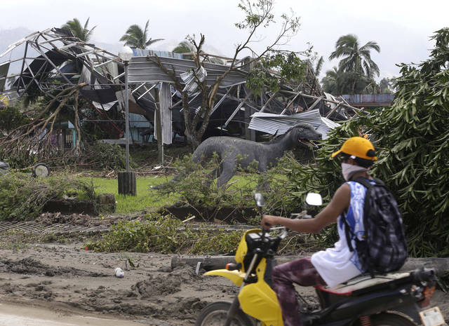 A resident cycles past a park which was damaged by the recent typhoon that hit New Bataan township, Compostela Valley in southern Philippines Sunday Dec. 9, 2012. The number of missing in the wake of the typhoon that devastated parts of the southern Philippines has jumped to nearly 900 after families and fishing companies reported losing contact with more than 300 fishermen in the South China Sea and Pacific Ocean, officials said Sunday.(AP Photo/Bullit Marquez)