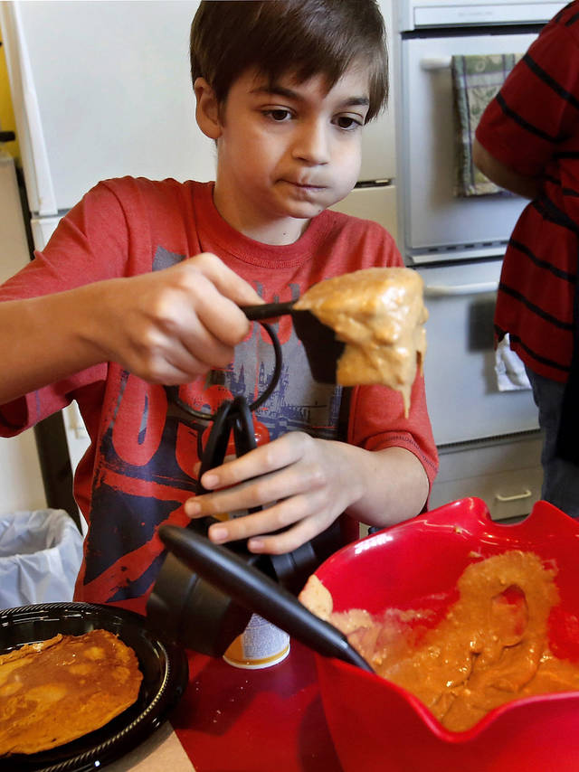 Zachary Jenkins, 11, fills a measuring cup with batter before pouring it into a skillet as he cooks pumpkin spice pancakes while competing in the Shawnee Mills&#039;  Kids&#039; Pancakes, Flapjacks and Griddle Cakes Contest at the Oklahoma State Fair on Saturday, Sep. 22, 2012. The event was held in the Creative Arts Building. Jenkins lives in Newalla and is a 6th grade home-schooled student.   Photo by Jim Beckel, The Oklahoman.