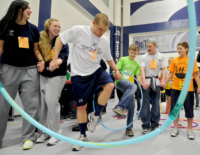 Four Diamonds family member Alex Smoker, 14, plays the hola hoop game with members of the Penn State volleyball and wrestling teams during athlete hour of the the Penn State IFC/Panhellenic Dance Marathon Saturday February 18, 2012, in State College, Pa. A tradition at Penn State is going on for the first time without Joe Paterno. The Hall of Fame football coach came each year to rouse 700 students trying to make it through the annual charity dance marathon on campus. (AP Photo/Centre Daily Times, Abby Drey) MANDATORY CREDIT; MAGS OUT