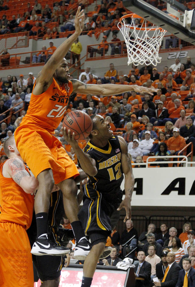 Missouri's Marcus Denmon (12) goes past Oklahoma State's Michael Cobbins (20) during an NCAA college basketball game between the Oklahoma State University Cowboys (OSU) and the Missouri Tigers (MU) at Gallagher-Iba Arena in Stillwater, Okla., Wednesday, Jan. 25, 2012. Photo by Bryan Terry, The Oklahoman
