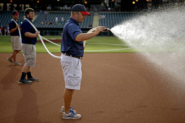 Monte McCoy, head groundskeeper of the Oklahoma City RedHawks, waters the field before a game at Chickasaw Bricktown Ballpark in Oklahoma City, Thursday, May 10, 2012. Photo by Bryan Terry, The Oklahoman