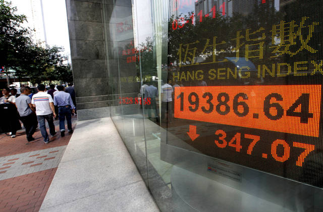People walk past a screen displaying the Hong Kong stock index's movement outside a local bank in Hong Kong Thursday, Nov. 3, 2011. Asian stock markets fell Thursday for the fourth straight day as a European deal to bail Greece out of its financial mess appeared to be on the verge of unraveling. (AP Photo/Vincent Yu) ORG XMIT: XVY101