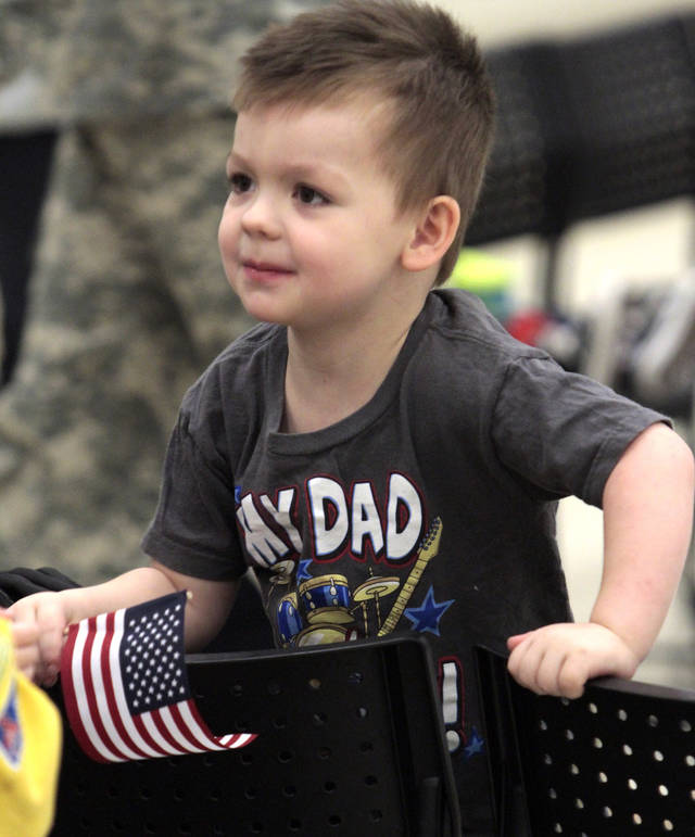 Trey Scott, 3, waits for his father, Spc. Galen Scott, to arrive as his dad and other members of the Oklahoma National Guard return from Afghanistan on Thursday, Jan. 12, 2012, in Norman, Okla.  His wife Jennifer is at right. Photo by Steve Sisney, The Oklahoman