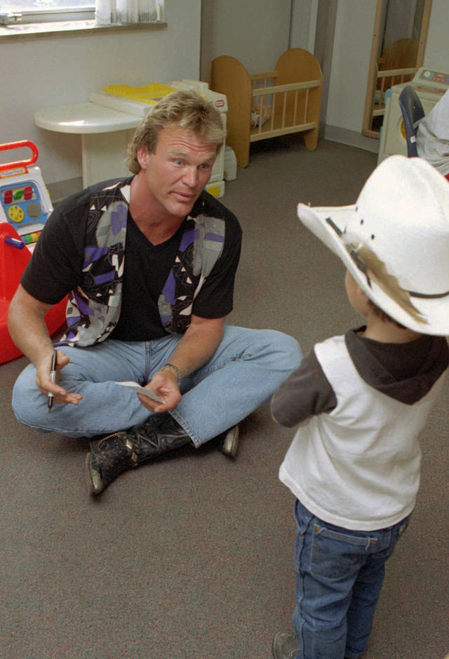 Former football star Brian Bosworth tries to coax patient  Jake Roller, 3, Del City, to sit in  his lap during Bosworth's visit to the Nicholson Tower surgery unit playroom at Children's Hospital of Oklahoma Friday afternoon. Bosworth was successful, as Roller eventually warmed up to himand sat in lap for an autograph.