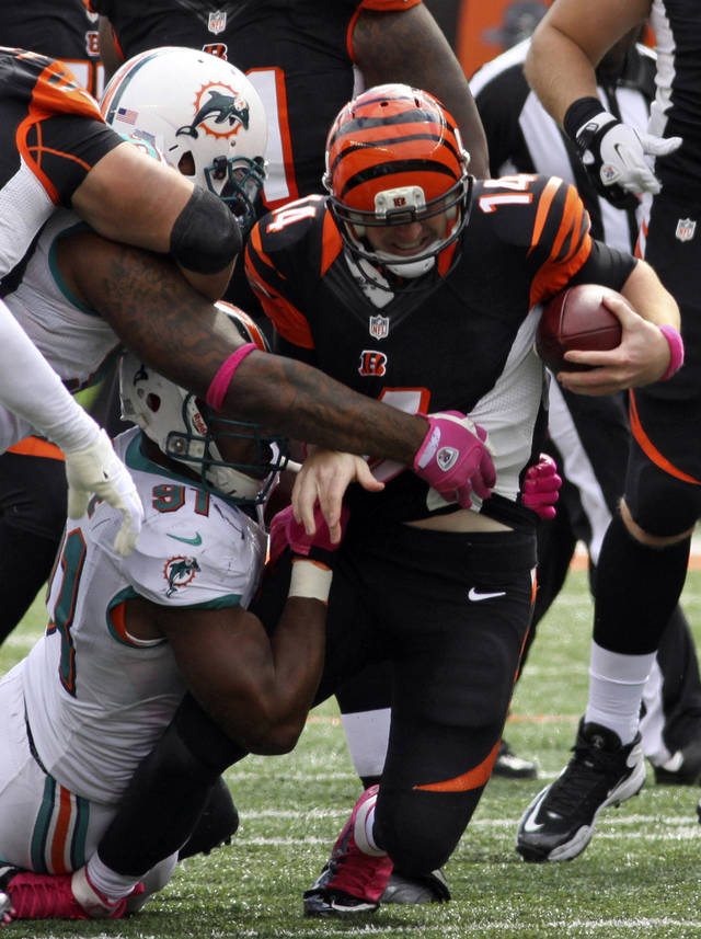 Cincinnati Bengals quarterback Andy Dalton (14) is sacked by Miami Dolphins defensive end Cameron Wake (91) in the second half of an NFL football game on Sunday, Oct. 7, 2012, in Cincinnati. (AP Photo/Tom Uhlman)