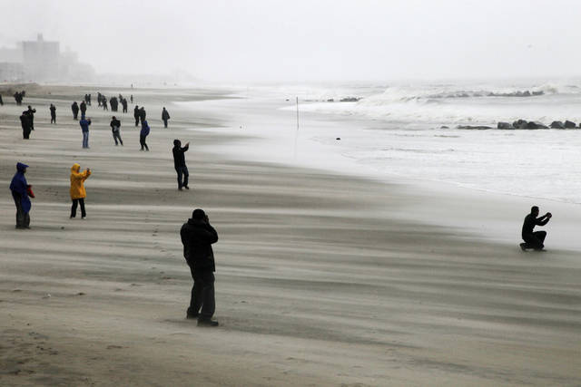 People brave high winds and blowing sand as they watch the rising surf at Coney Island Beach in the Brooklyn borough of New York as Hurricane Sandy arrives, Monday, Oct. 29, 2012. Hurricane Sandy continued on its path Monday, as the storm forced the shutdown of mass transit, schools and financial markets, sending coastal residents fleeing, and threatening a dangerous mix of high winds and soaking rain. (AP Photo/Mark Lennihan) ORG XMIT: NYML111