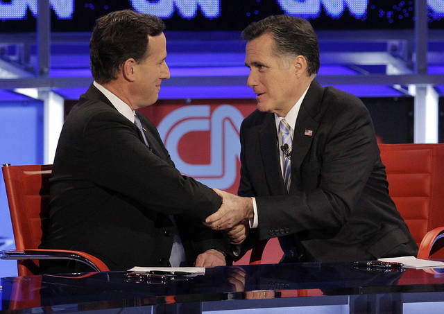 FILE - In this Feb. 22, 2012, file photo Republican presidential candidate and former Massachusetts Gov. Mitt Romney, right, talks with fellow candidate, former Pennsylvania Sen. Rick Santorum, left, after a presidential debate in Arizona. Romney on Friday met privately with Santorum, who has indicated he will ultimately endorse Romney. Since the day Santorum left the race, Romney's campaign has been recruiting former Santorum staffers and courting his key allies, including his donors. (AP Photo/Jae C. Hong, File)