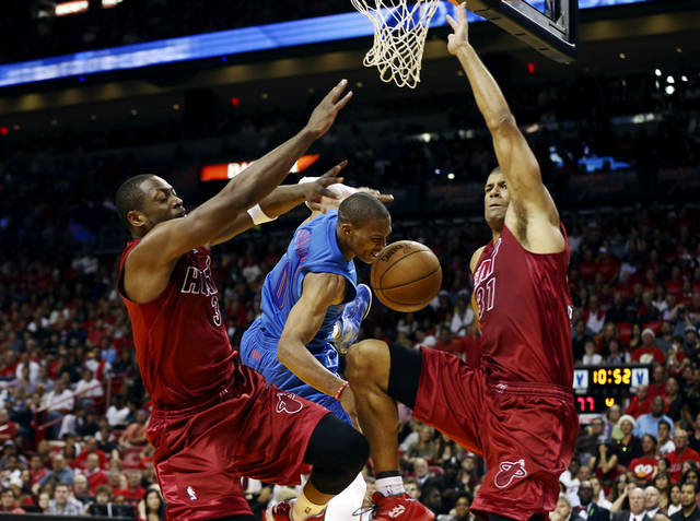 Miami Heat's Dwyane Wade (3) and Shane Battier (31) block Oklahoma City Thunder's Russell Westbrook (0) during the second half of an NBA basketball game in Miami, Tuesday, Dec. 25, 2012. The Heat won 103-97. (AP Photo/J Pat Carter) ORG XMIT: FLJC111
