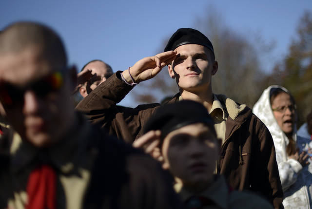 Boy Scout Michael Demanche, of Mashpee, Mass., salutes the flag during a ceremony held at the National Cemetery in Bourne, Mass., Saturday, Nov. 10, 2012. Following the ceremony, Demanche joined hundreds of volunteers in placing thousands of U.S. flags at the graves of deceased veterans in advance of Veterans Day. (AP Photo/Gretchen Ertl)