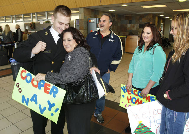 U.S. Naval Academy cadet Cooper Ansell gets a hug from his mom, Susan Ansell, as he arrives home for the holidays at Will Rogers World Airport in Oklahoma City on Tuesday. With them are his dad, Craig, sister, Stephanie, and girlfriend, Konnar Hodges.