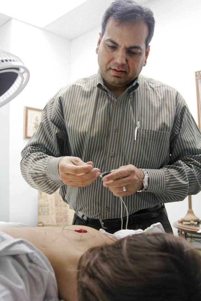 Amit Gumman, of Harmony Healing Center, performs acupuncture on Claire Ragozzino, 24, of Oklahoma City. <strong>Jaclyn Cosgrove</strong>