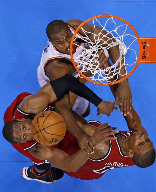 Oklahoma City's Serge Ibaka (9) fights for the ball with Miami's Dwyane Wade (3) and Chris Bosh (1) during an NBA basketball game between the Oklahoma City Thunder and the Miami Heat at Chesapeake Energy Arena in Oklahoma City, Thursday, Feb. 15, 2013. Miami won 110-100. Photo by Bryan Terry, The Oklahoman