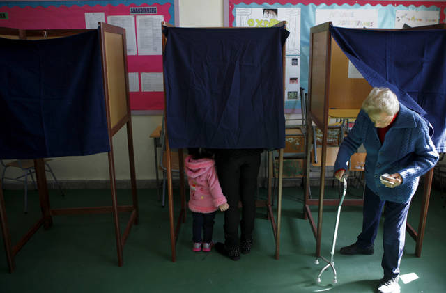 A woman, right, leaves a polling booth as a mother with her child votes in an other booth in the Presidential election in southern port city of Limassol, Cyprus, Sunday, Feb. 17, 2013. Cypriots are voting Sunday for a new president who must tackle a financial crisis that has forced the country to seek international rescue money to stay solvent.  (AP Photo/Petros Karadjias)