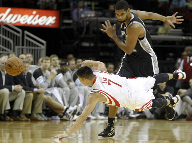 Rockets Jeremy Lin (7) scrambles for the ball against Spurs Tim Duncan (21) during the first half of an NBA basketball game, Sunday, Oct. 14, 2012, in Houston. (AP Photo/Eric Kayne)