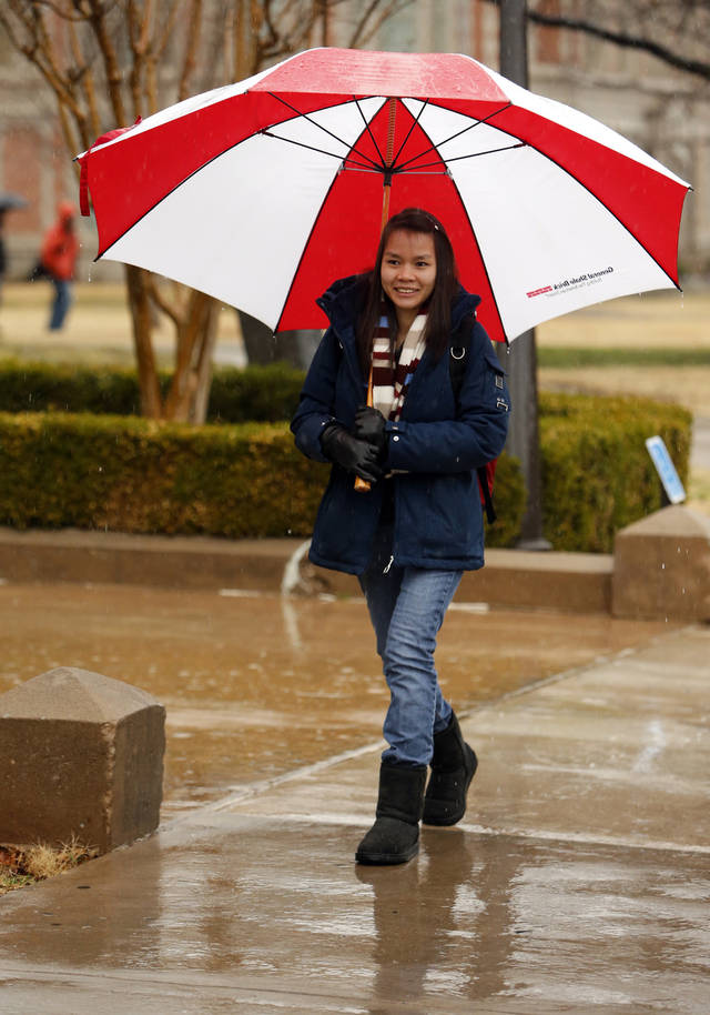 Hue Kimle has room to spare under umbrella as students head to class in the rain on the campus of the University of Oklahoma (OU) on Tuesday, Feb. 12, 2013 in Norman, Okla.  Photo by Steve Sisney, The Oklahoman